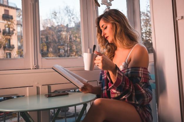 Stile di vita di una giovane bionda che fa colazione accanto alla vendita della sua casa. vestito in mutande e pigiama, leggendo un libro la mattina