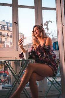 Stile di vita di una giovane bionda che fa colazione accanto alla vendita della sua casa. vestito in mutande e pigiama, sorridendo a un social diretto