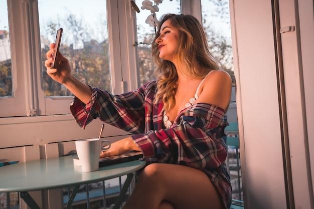 Stile di vita di una giovane bionda che fa colazione accanto alla vendita della sua casa. vestito in mutande e pigiama, sorridente in una videochiamata