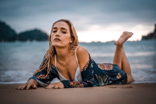 Stile di vita, giovane bionda sdraiata sulla sabbia sulla spiaggia con bikini bianco. nei paesi baschi