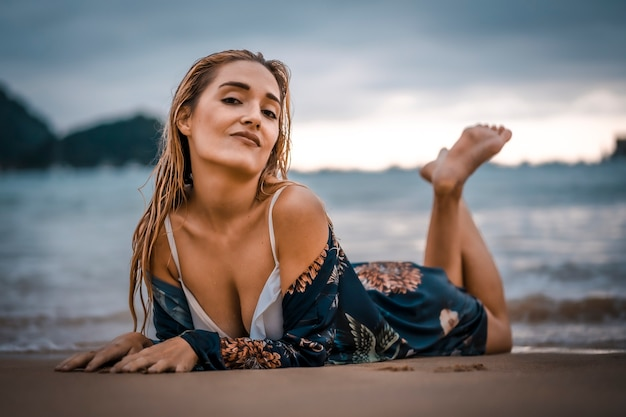 Stile di vita, giovane bionda sdraiata sulla sabbia sulla spiaggia con bikini bianco. a san sebastian, paesi baschi