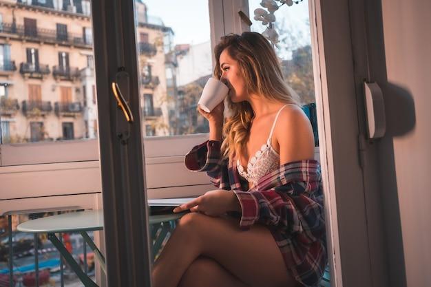 Stile di vita di una giovane donna bionda che fa colazione accanto alla vendita della sua casa. vestito in biancheria intima e pigiama, bevendo caffè in un drink e leggendo un libro