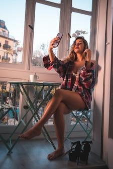 Stile di vita di una giovane donna bionda che fa colazione accanto alla vendita della sua casa. vestito in biancheria intima e pigiama, con una bevanda al caffè e facendo un selfie