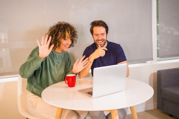 Stile di vita, una giovane coppia caucasica in pigiama facendo colazione in cucina, facendo una videochiamata di famiglia sul computer, una nuova normalità