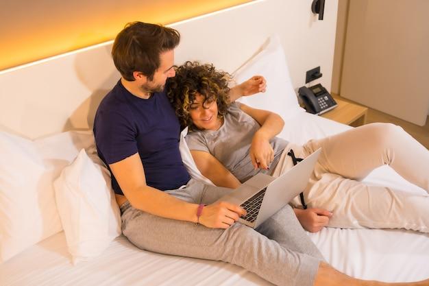 Lifestyle, una giovane coppia caucasica, con sguardi complici in pigiama sopra, coccolata in pigiama sul letto guardando il computer
