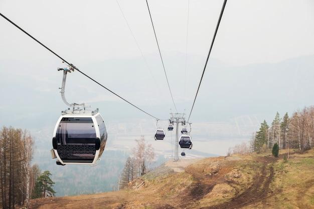 Cabine di sollevamento in una stazione sciistica di montagna funivia in montagna stazione invernale di montagna in una giornata nuvolosa seggiovia funivia con persone panoramica panoramica ampia vista sulle piste da discesa