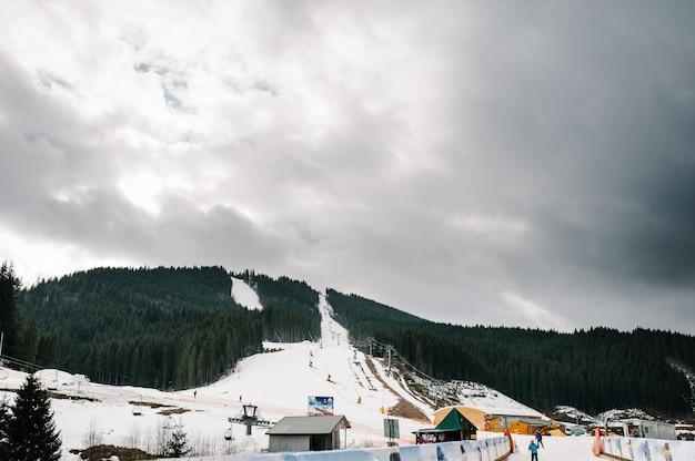 L'impianto di risalita in montagna per il pattinaggio sugli sci. sullo sfondo del bosco, il bianco della neve e le case.