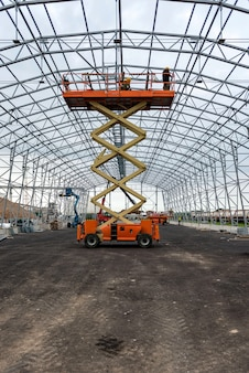 Sollevi con il lavoro della piattaforma nel campo di costruzione del capannone del magazzino.
