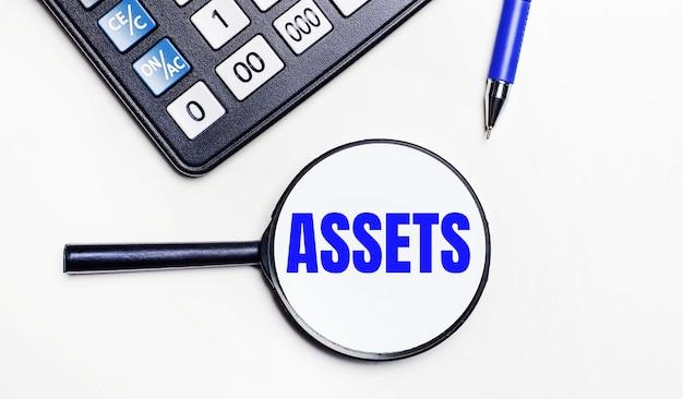 Su uno sfondo chiaro, una calcolatrice nera, una penna blu e una lente d'ingrandimento con testo all'interno della parola asset. vista dall'alto