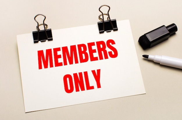 Su uno sfondo chiaro, un pennarello nero aperto e su clip nere un foglio di carta bianco con il testo solo membri