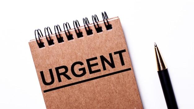 Su uno sfondo chiaro, una penna nera e un taccuino marrone su molle nere con la scritta urgent