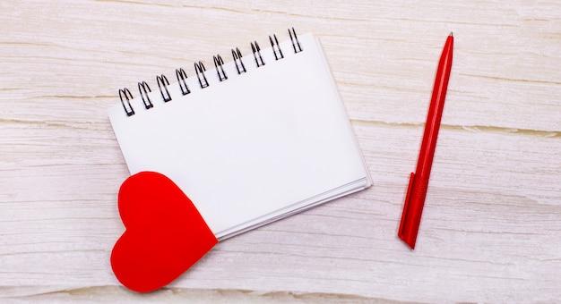 Su uno sfondo chiaro, un taccuino vuoto, cuori rossi e una penna rossa. luogo per inserire testo o illustrazioni