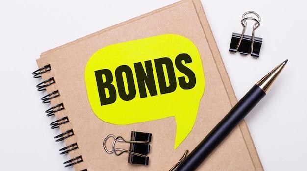 Su uno sfondo chiaro, un taccuino marrone, una penna nera e graffette e un cartellino giallo con il testo bonds. concetto di affari.