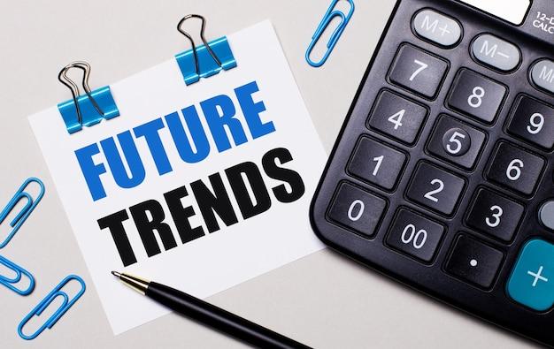 Su uno sfondo chiaro, una calcolatrice, una penna, graffette blu e un foglio di carta con il testo tendenze future. vista dall'alto