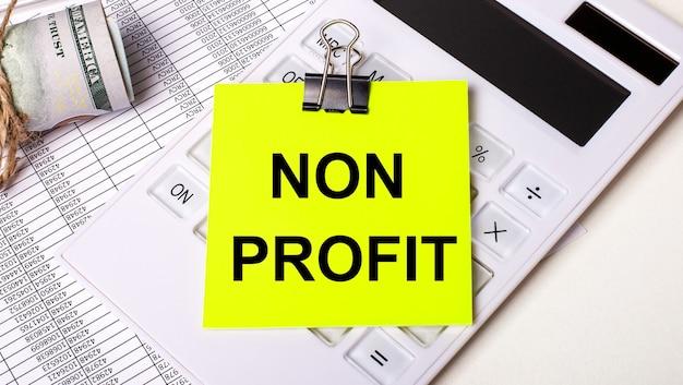 Su uno sfondo chiaro - contanti, una calcolatrice bianca e un adesivo giallo sotto una graffetta nera con il testo non profit. concetto di affari