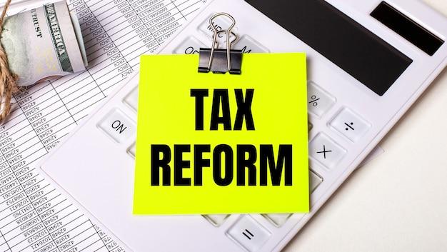 Su uno sfondo chiaro - contanti, una calcolatrice bianca e un adesivo giallo sotto una graffetta nera con il testo riforma fiscale. concetto di affari