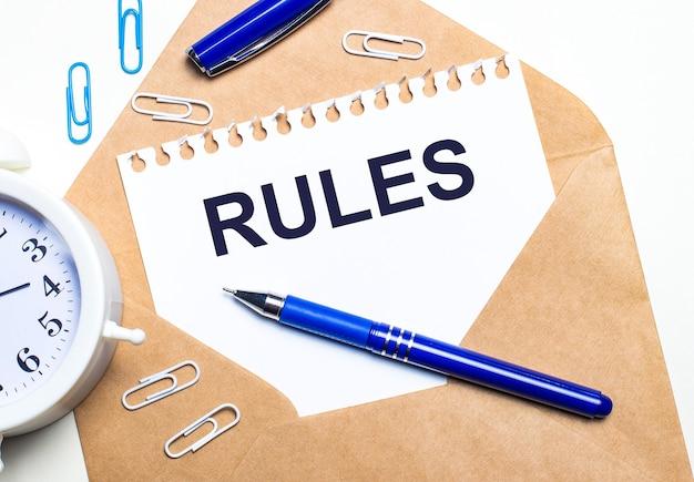 Su uno sfondo chiaro, una busta artigianale, una sveglia, graffette, una penna blu e un foglio di carta con la scritta rules.