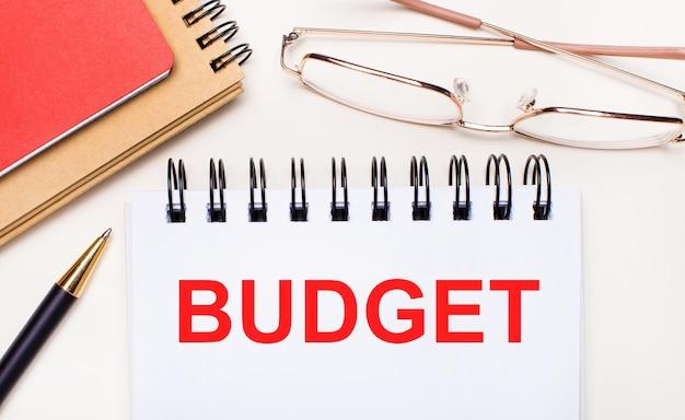 Su uno sfondo chiaro - occhiali con montatura dorata, una penna, taccuini marroni e rossi e un taccuino bianco con il testo budget. concetto di affari