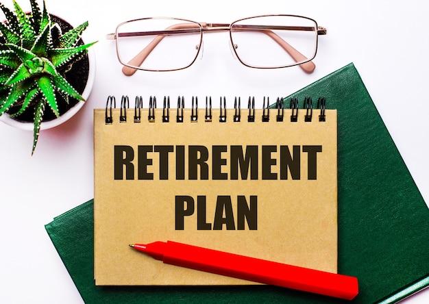 Su uno sfondo chiaro, occhiali con montatura dorata, un fiore in vaso, un taccuino verde, una penna rossa e un taccuino marrone con la scritta piano pensione. concetto di affari