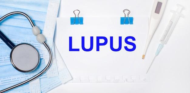 Su uno sfondo chiaro si trovano uno stetoscopio, un termometro elettronico, una siringa, una maschera facciale e un foglio di carta con il testo lupus. concetto medico