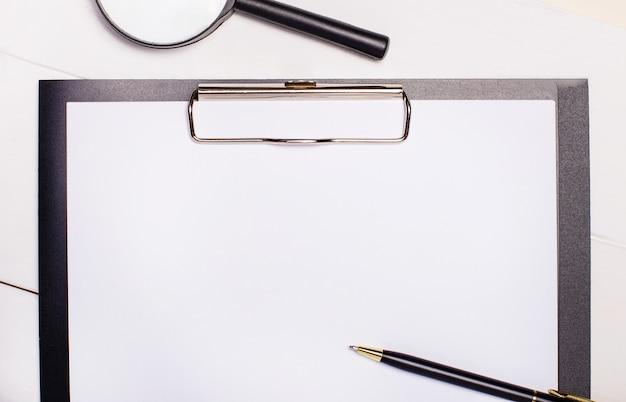 Su uno sfondo chiaro, una lente d'ingrandimento, carta e penna con un posto per inserire il testo. concetto di affari