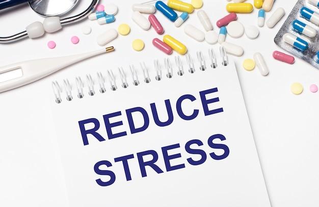 Su uno sfondo chiaro, pillole multicolori, uno stetoscopio, un termometro elettronico e un quaderno con la scritta riduci lo stress. concetto medico.