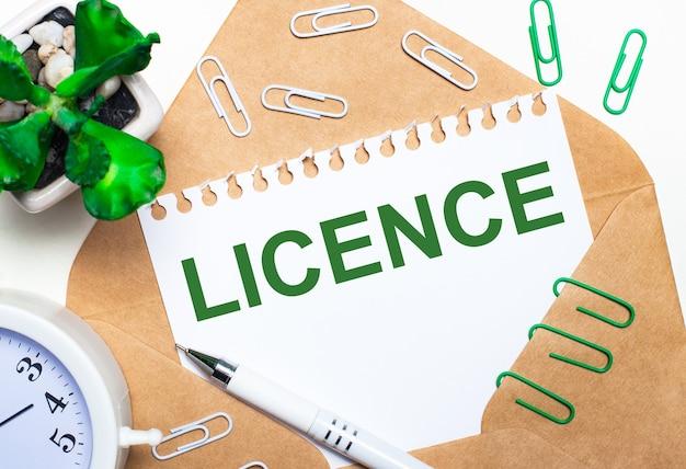 Su uno sfondo chiaro, una busta aperta, una sveglia bianca, una pianta verde, graffette bianche e verdi, una penna bianca e un foglio di carta con il testo licenza