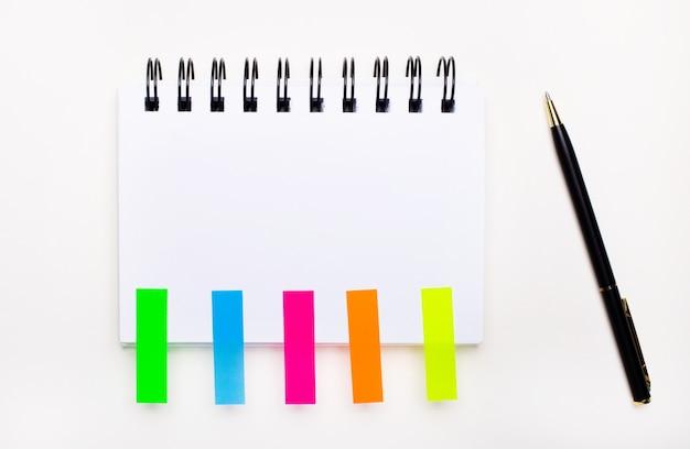 Su uno sfondo chiaro, una penna, un quaderno con uno spazio per inserire testo e adesivi luminosi. modello