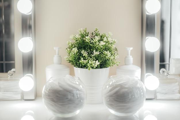 Sfondo chiaro e posto per truccatore, una lampadina di vetro con un dischetto di cotone