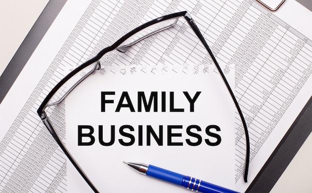 Su sfondo chiaro, una relazione, occhiali con montatura nera, una penna e un foglio di carta con la scritta affari di famiglia. concetto di affari