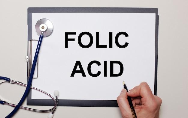 Su uno sfondo chiaro, uno stetoscopio e un foglio di carta, su cui un uomo scrive acido folico. concetto medico