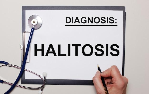 Su uno sfondo chiaro, uno stetoscopio e un foglio di carta, su cui un uomo scrive alitosi. concetto medico