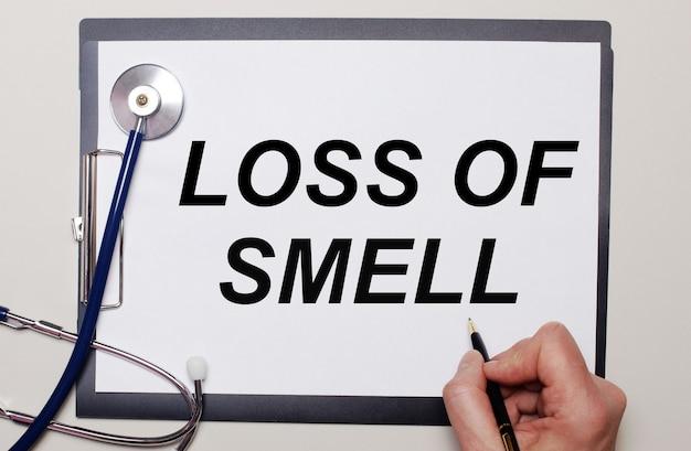Su uno sfondo chiaro, uno stetoscopio e un foglio di carta, su cui un uomo scrive perdita di odore. concetto medico