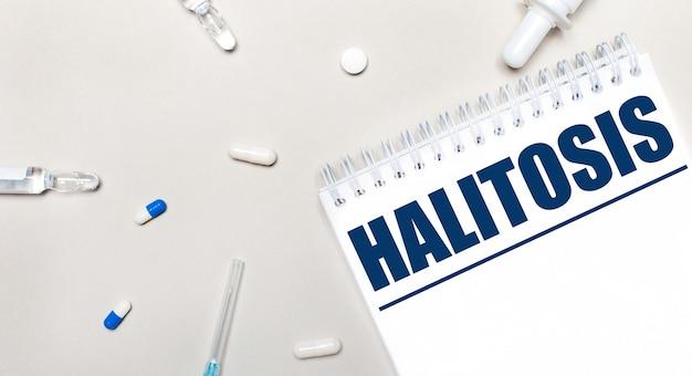 Su uno sfondo chiaro, uno stetoscopio, fiale di medicinali e un blocco note bianco con la scritta halitosis