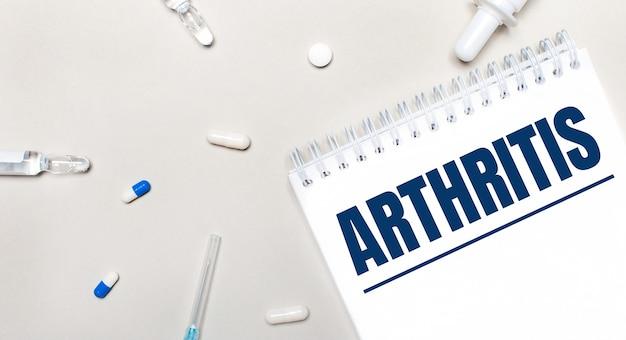 Su uno sfondo chiaro, una siringa, uno stetoscopio, fiale di medicinali, un'ampolla e un blocco note bianco con la scritta artrite. concetto medico
