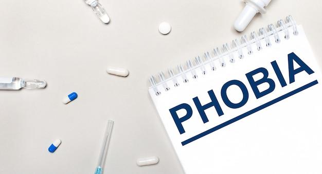 Su uno sfondo chiaro, una siringa, uno stetoscopio, fiale di medicinali, un'ampolla e un blocco note bianco con la scritta phobia. concetto medico