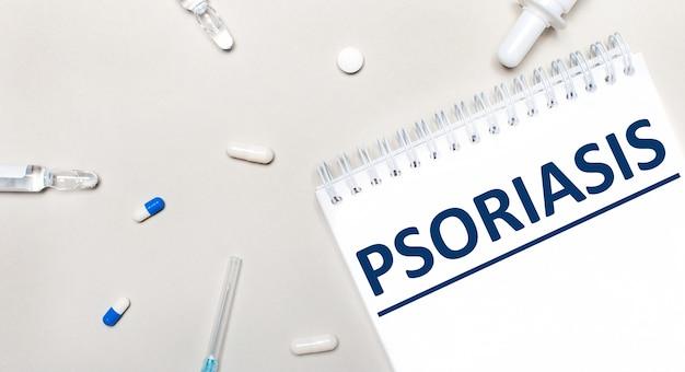 Su uno sfondo chiaro, una siringa, uno stetoscopio, fiale di medicinale, un'ampolla e un blocco note bianco con la scritta psoriasis. concetto medico