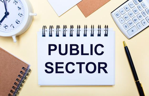 Su uno sfondo chiaro, una sveglia bianca, una calcolatrice, una penna e un taccuino con la scritta settore pubblico. lay piatto