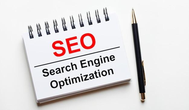 Su uno sfondo chiaro, un taccuino bianco con le parole seo search engine optimization e una penna.