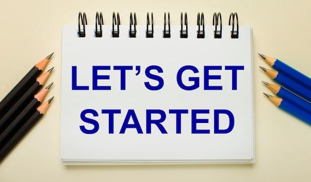 Su uno sfondo chiaro, un quaderno bianco con la scritta let is get started e matite nere e blu ai lati.