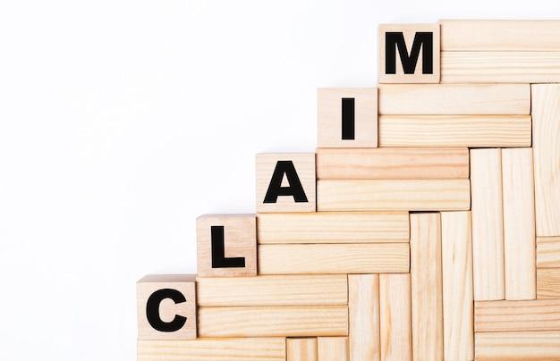 Su uno sfondo chiaro, blocchi di legno e cubi con la scritta claim