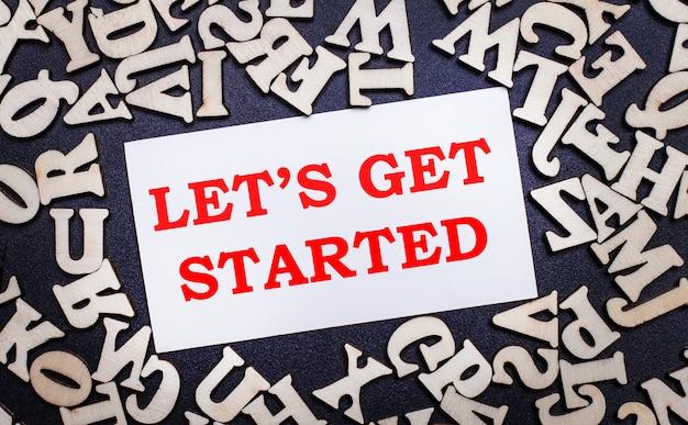 Su uno sfondo chiaro, lettere in legno dell'alfabeto inglese e un cartoncino bianco all'interno con la scritta let is get started