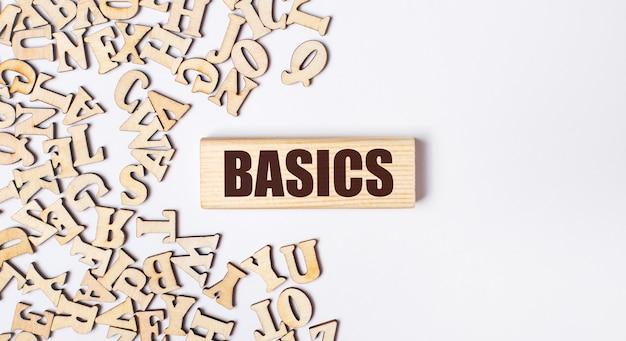 Su uno sfondo chiaro, lettere in legno e un blocco di legno con il testo basics. lay piatto