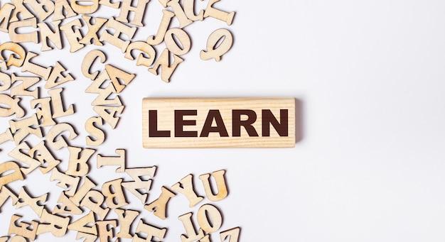 Su uno sfondo chiaro, lettere di legno e un blocco di legno con il testo learn. lay piatto