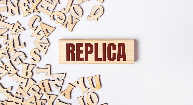Su fondo chiaro, lettere in legno e un blocco di legno con la scritta replica. lay piatto