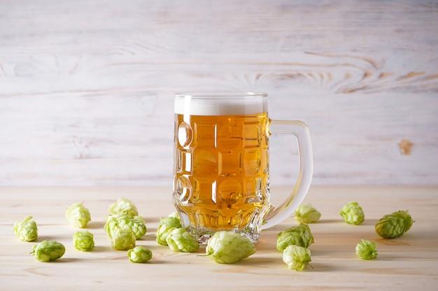 Birra leggera in bicchiere e coni di luppolo su tavola di legno.