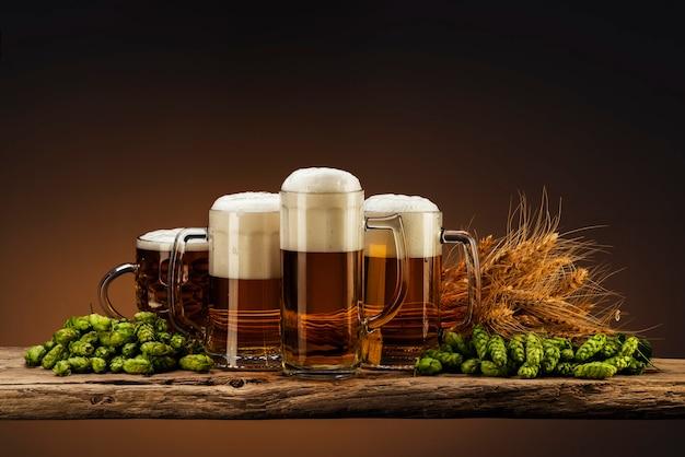 Birra leggera in bicchieri con luppolo e grano su una tavola di legno