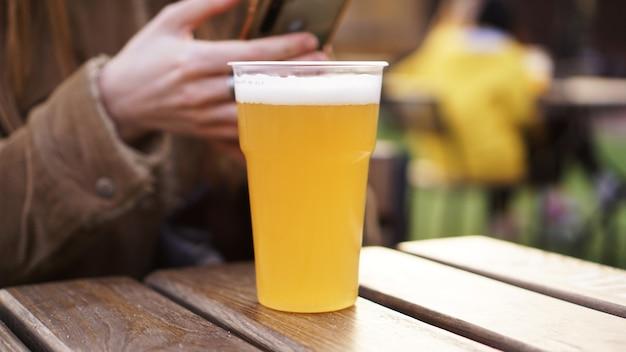Birra leggera in un bicchiere di plastica ragazza che beve birra al food court
