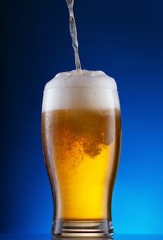 Birra leggera che versa nel vetro sul blu