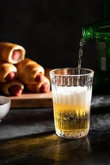 La birra chiara si versa in un bicchiere. salsicce nell'impasto sulla tavola in sottofondo